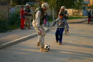 soldier plays soccer with iraqi boy